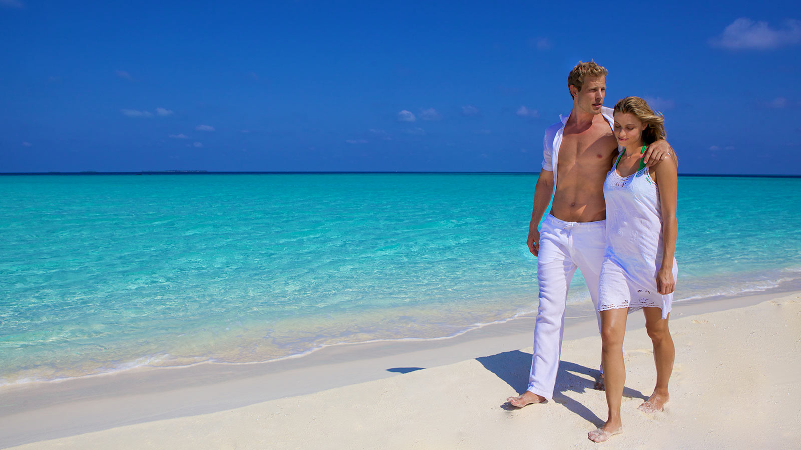 kuredu-couple-walking-on-the-beach-in-white-1600x900